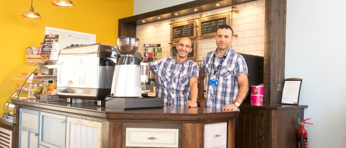 Two baristas stand behind counter of the coffee shop at the New QEII Hospital